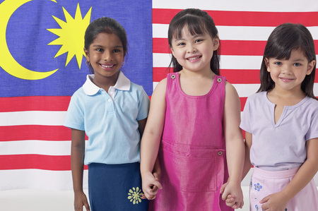 Young Malay, Chinese and Indian girls holding hands in front of Malaysian flag
