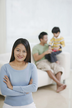 family sofa: Woman posing with her arms folded, man playing with boy in the background