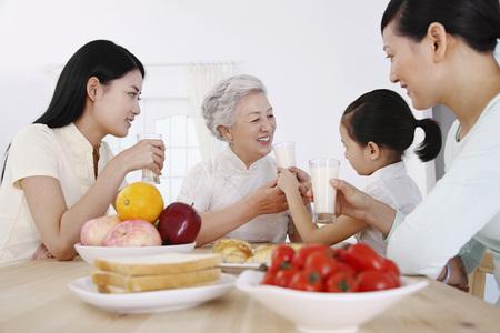 Senior woman, women and girl having breakfast together Stock Photo