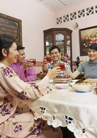 Guests enjoying feast on Hari Raya open house Stock Photo
