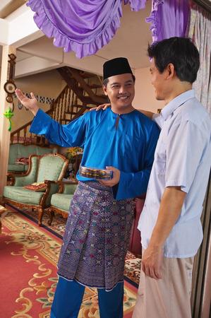 Malay man welcoming guest to Hari Raya open house Stock Photo