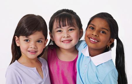 De jeunes filles malaises, chinoises et indiennes se sourient et s'étreignent