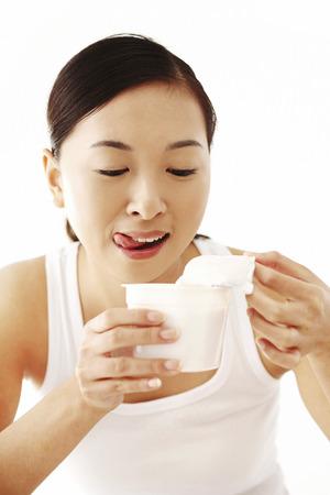 Woman holding a tub of yoghurt Stock Photo