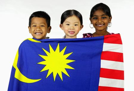 マレー、中国、インドの子供たちが Malaydian 旗を掲げている