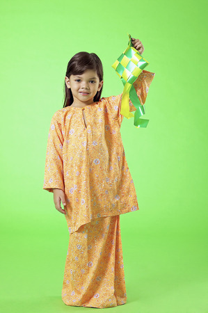 Young Malay girl in baju kurung holding ketupat