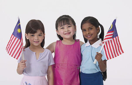 Young Malay, Chinese and Indian girls holding Malaysian flag