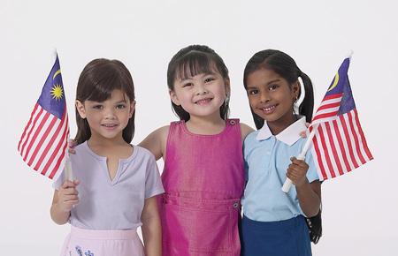 Jeunes filles malaises, chinoises et indiennes tenant un drapeau malaisien