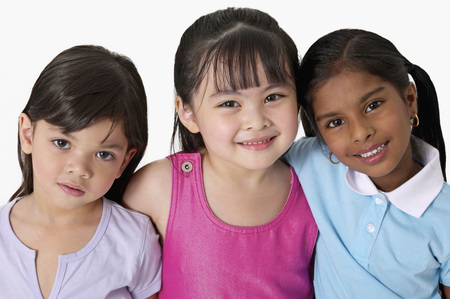 Young Malay, Chinese and Indian girls smiling and hugging each other