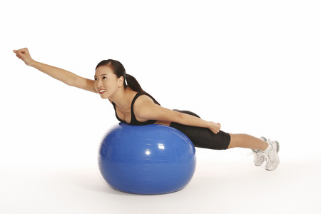 Young woman lying forward on fitness ball