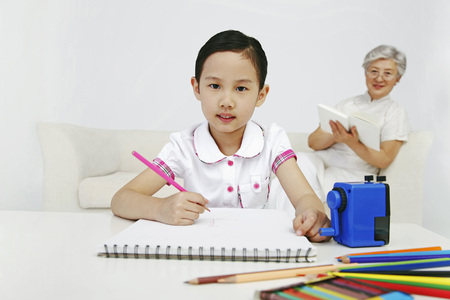 family sofa: Girl drawing on sketchbook while senior woman is reading book in the background