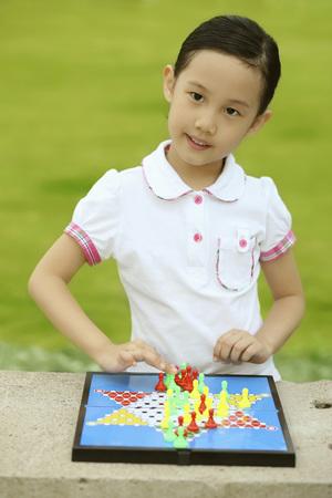 Girl playing chinese checkers Stock Photo
