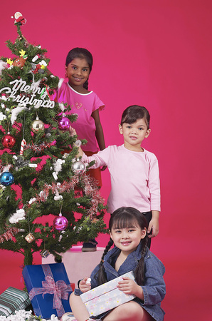Young girls decorating Christmas tree