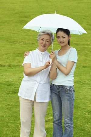 Senior woman and woman posing with umbrella Stock Photo