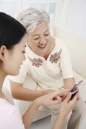 Woman showing senior woman text message on the phone Stock Photo