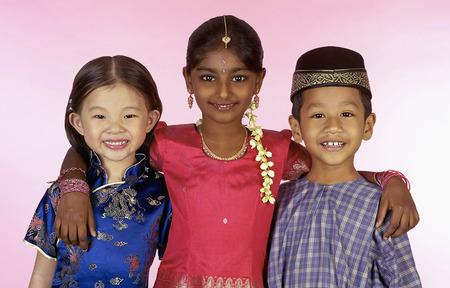 Jonge Maleise, Chinese en Indische kinderen in traditionele kleding die elkaar glimlachen en koesteren