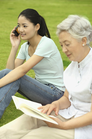 Senior woman reading book while woman is talking on the phone