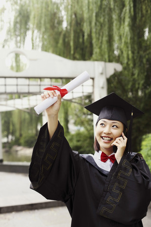 Woman in graduation robe talking on the phone