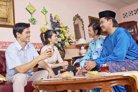 Malay couple entertaining guests on Hari Raya open house