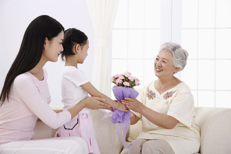 family sofa: Girl giving a bouquet of flowers to senior woman, woman guiding girl