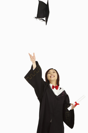 Woman in graduation robe throwing mortarboard