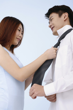 Woman helping guy to put on his necktie