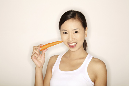 Woman holding a carrot Stock Photo