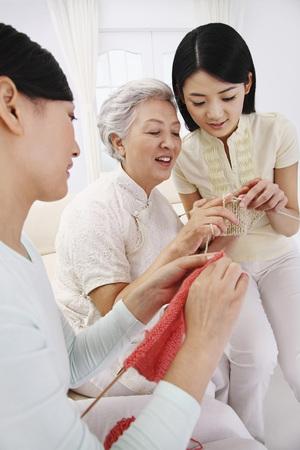 family sofa: Senior woman teaching women how to knit