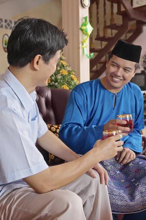Malay man entertaining his guest on Hari Raya open house Stock Photo