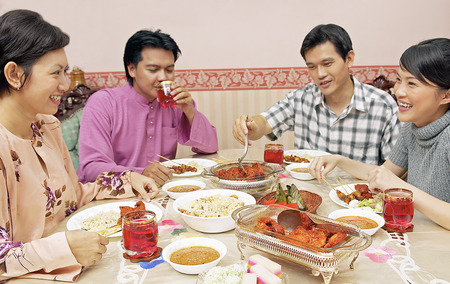 Guests enjoying feast on Hari Raya open house Stock Photo