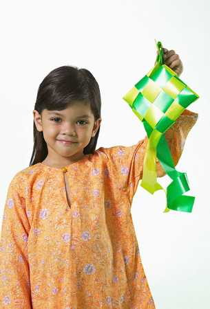 Young Malay girl in baju kurung holding ketupat
