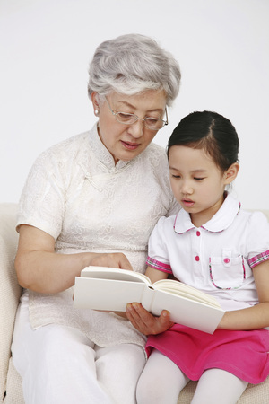 Senior woman and girl reading together