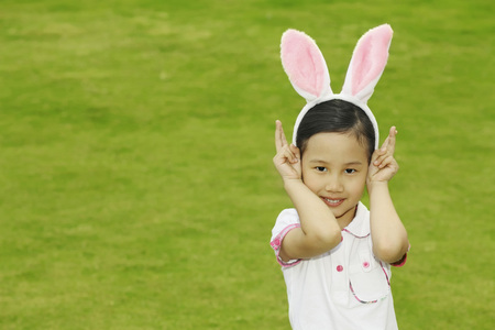 Girl wearing bunny headband showing peace sign Stock Photo