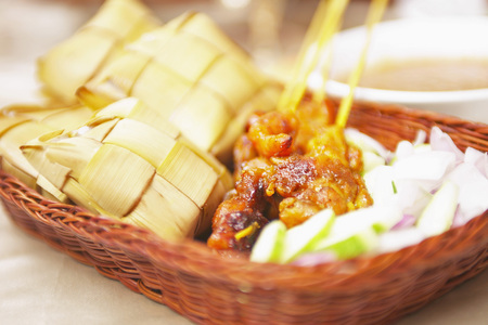 close up of onions in a basket: Satay and ketupat dish