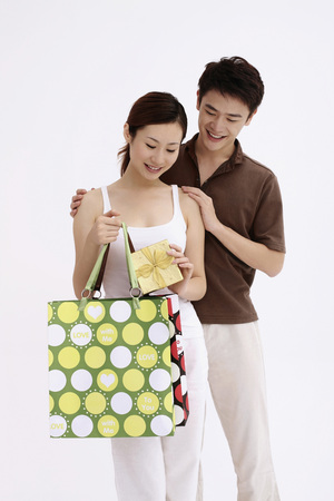 Woman taking out present from the paperbag, man watching