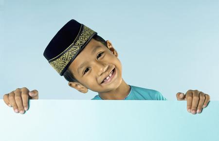 Young Malay boy with songkok peeking over board