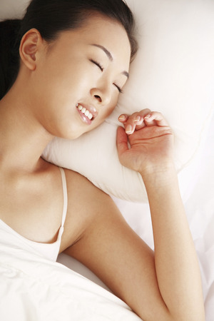 Woman lying on bed with her eyes closed