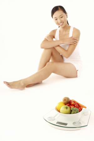 A bowl of fruits and vegetables on weight scale with woman sitting in the background