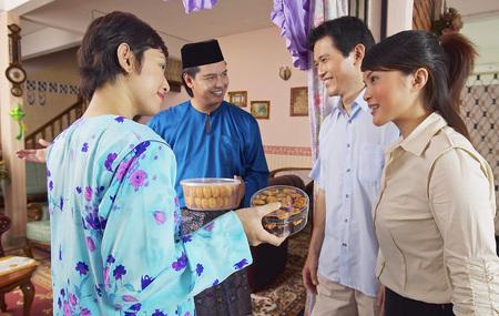 Couple malais accueillant des invités sur Hari Raya portes ouvertes Banque d'images