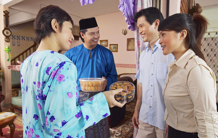 Het Maleise paar verwelkomt gasten op de open dag van Hari Raya Stockfoto