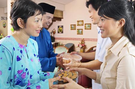 Malay couple welcoming guests on Hari Raya open house