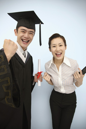 jubilating: Man in mortarboard and graduation gown celebrating with woman