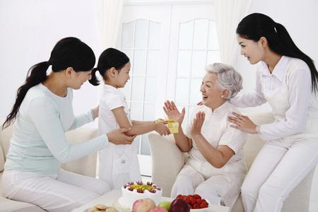 Women watching girl giving present to senior woman Stock Photo