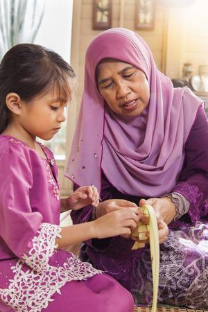 Muslim family weaving ketupat Stock Photo