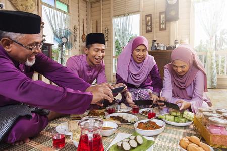 Familia musulmana tomando fotografías de la comida durante el Eid al-Fitr