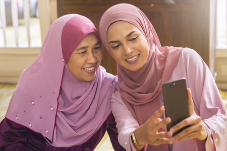 Malay woman taking self-photograph with her parent