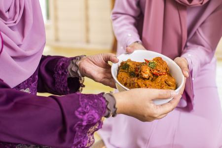 Muslim women holding a bowl of chicken rendang Stock Photo