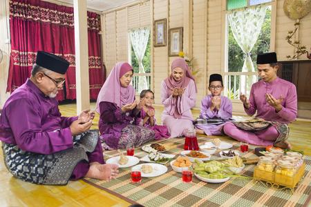 Muslim family saying prayers before meal Stock Photo