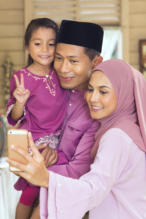 Malay family taking self-photograph with a smartphone