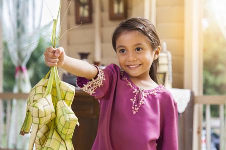 Muslim girl holding ketupats