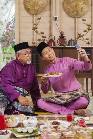 Malay man taking self-photograph with his parent